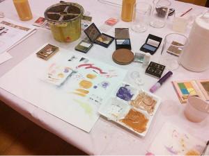 集まった化粧品とそれを絵具化したもの。アイシャドウが中心のため、色の数は多い