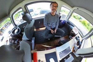独立型ソーラーの実践者を訪ねて全国取材の旅に出る新井さんと軽自動車の車内(新井由己さん提供)