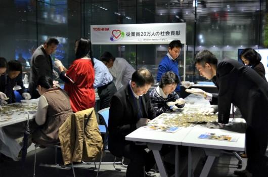 ワークショップコーナー。有志が国連ハビタット協会と共に、国際線空港の募金箱に集まった世界のコインを仕分けした