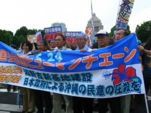 人間の鎖行動で国会前に集まった沖縄選出の国会議員ら=24日