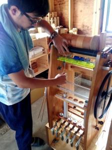 糸紡ぎ小屋を案内してくれた酒井悠太さん。再現されたガラ紡機