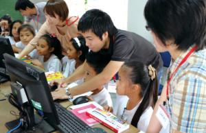 子どもたちにパワーポイントの使い方を教える高濱氏(中央)