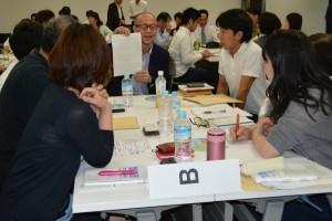 各グループごとに学びを共有する、写真奥は、講師の藤原慎太郎・トヨタ自動車業務品質改善部第1TQM室主査