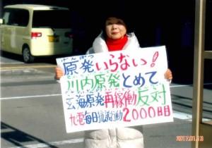 「原発いらない!」とボードを掲げる島田雅美さん
